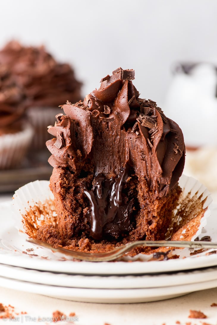 A triple chocolate cupcake on a stack of three white plates, with a bite taken out of it. The decadent chocolate fudge sauce oozes out of the middle.