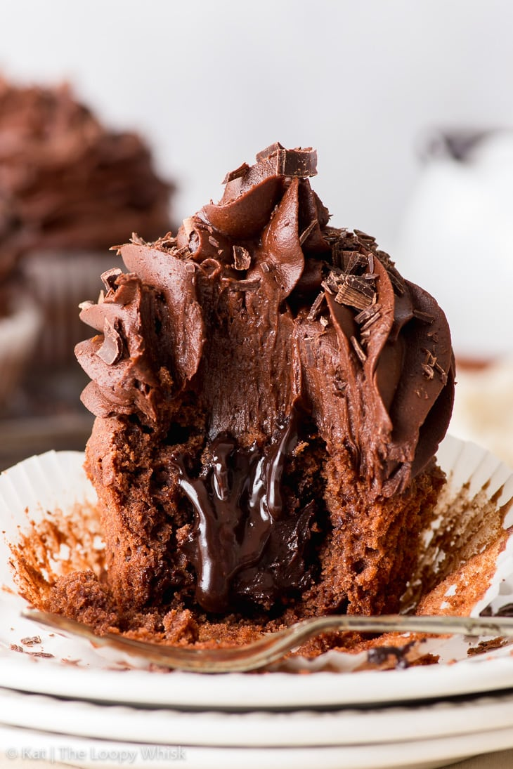 Close-up of a triple chocolate cupcake on a stack of three white plates, with a bite taken out of it. The decadent chocolate fudge sauce oozes out of the middle.