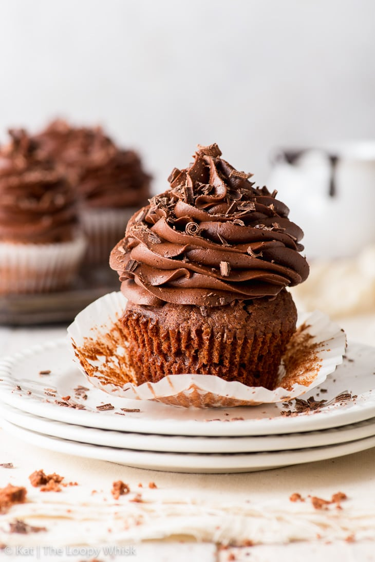 A triple chocolate cupcake on a stack of three white plates, with its cupcake liner partially peeled away, with more cupcakes in the background.