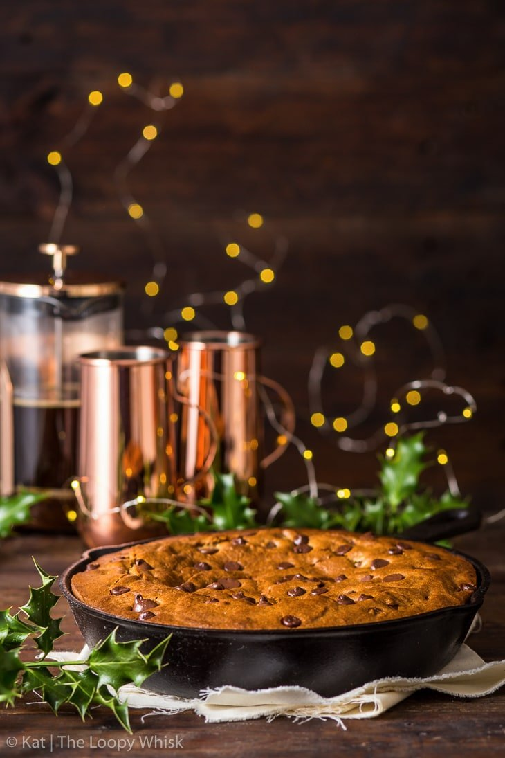 Chocolate chip gingerbread skillet cookie on a dark brown surface, with a dark brown background. Sprigs of holly and fairy lights in the background.