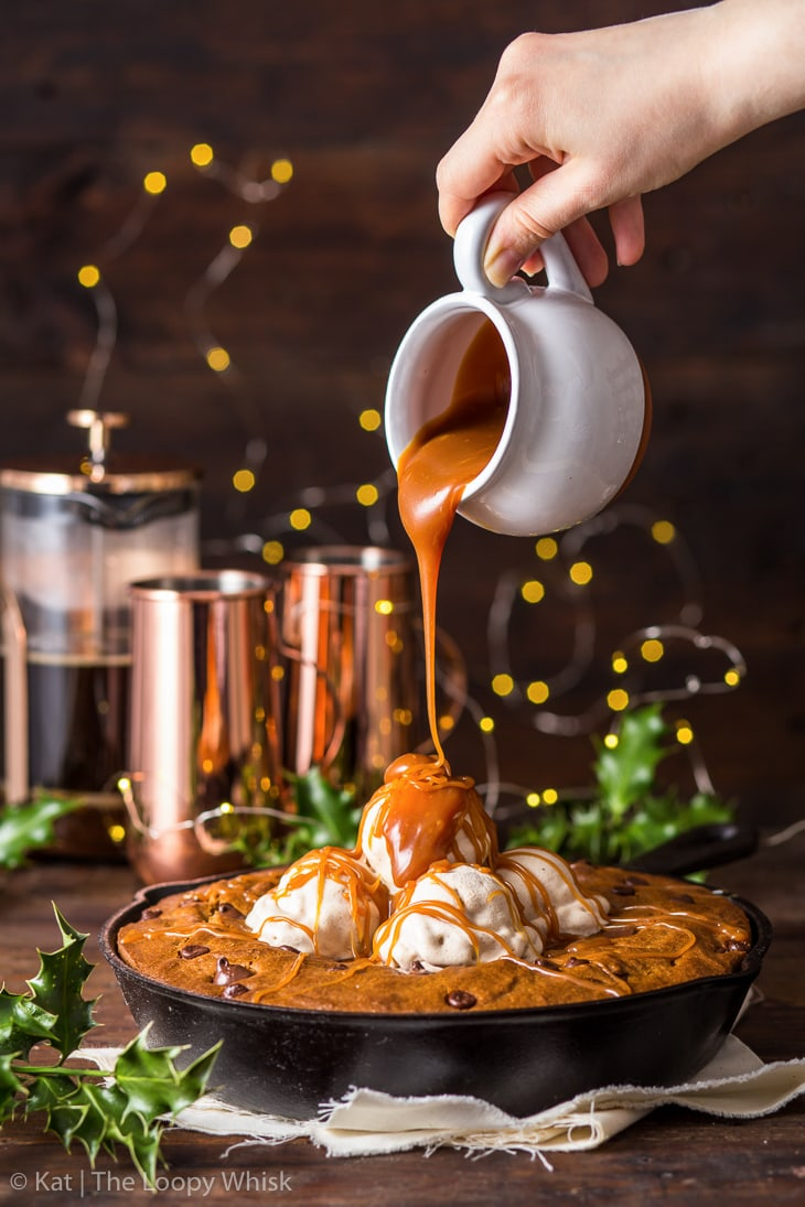 Gingerbread skillet cookie topped with cinnamon ice cream, being drizzled with caramel sauce.