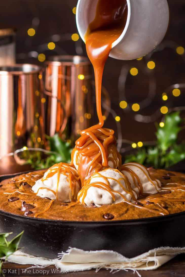Close-up of the gingerbread skillet cookie topped with cinnamon ice cream, being drizzled with caramel sauce.