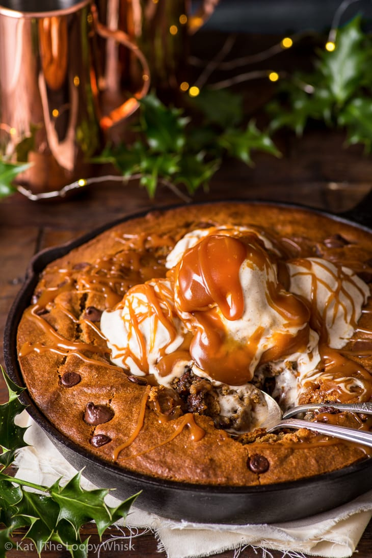 Gingerbread skillet cookie topped with slightly melted cinnamon ice cream and drizzled with caramel sauce. It's been partially eaten, two spoons in the skillet.