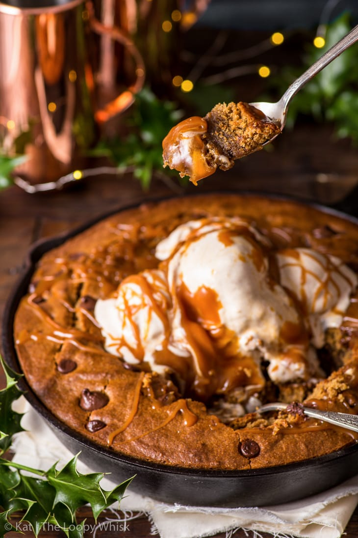 Gingerbread skillet cookie topped with slightly melted cinnamon ice cream and drizzled with caramel sauce. It's been partially eaten, a bite on a spoon above the skillet.