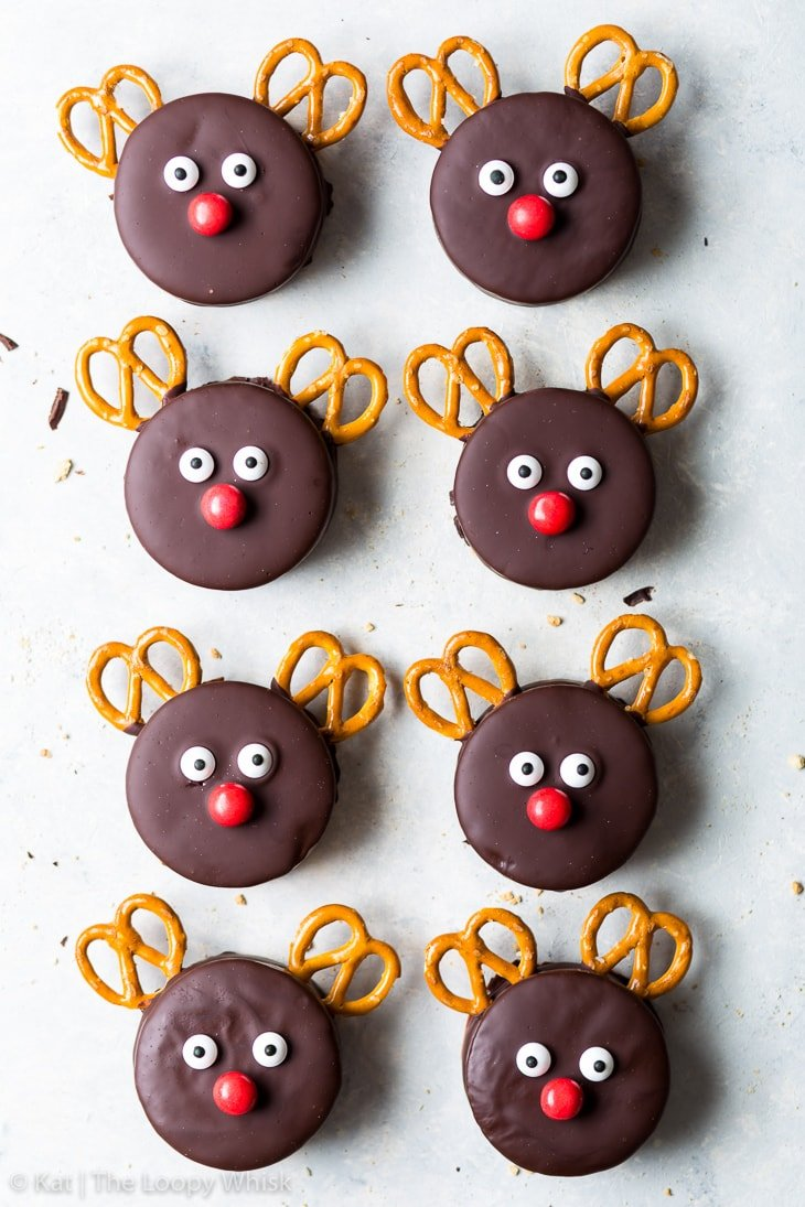 Overhead view of a regular array of eight Rudolph cookies, in two columns of four, on a white surface.