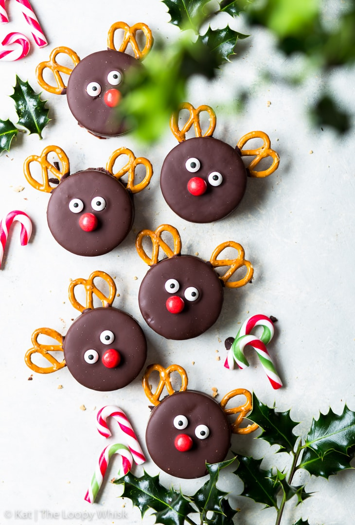 Overhead view of Rudolph cookies, surrounded my small candy canes and sprigs of holly.