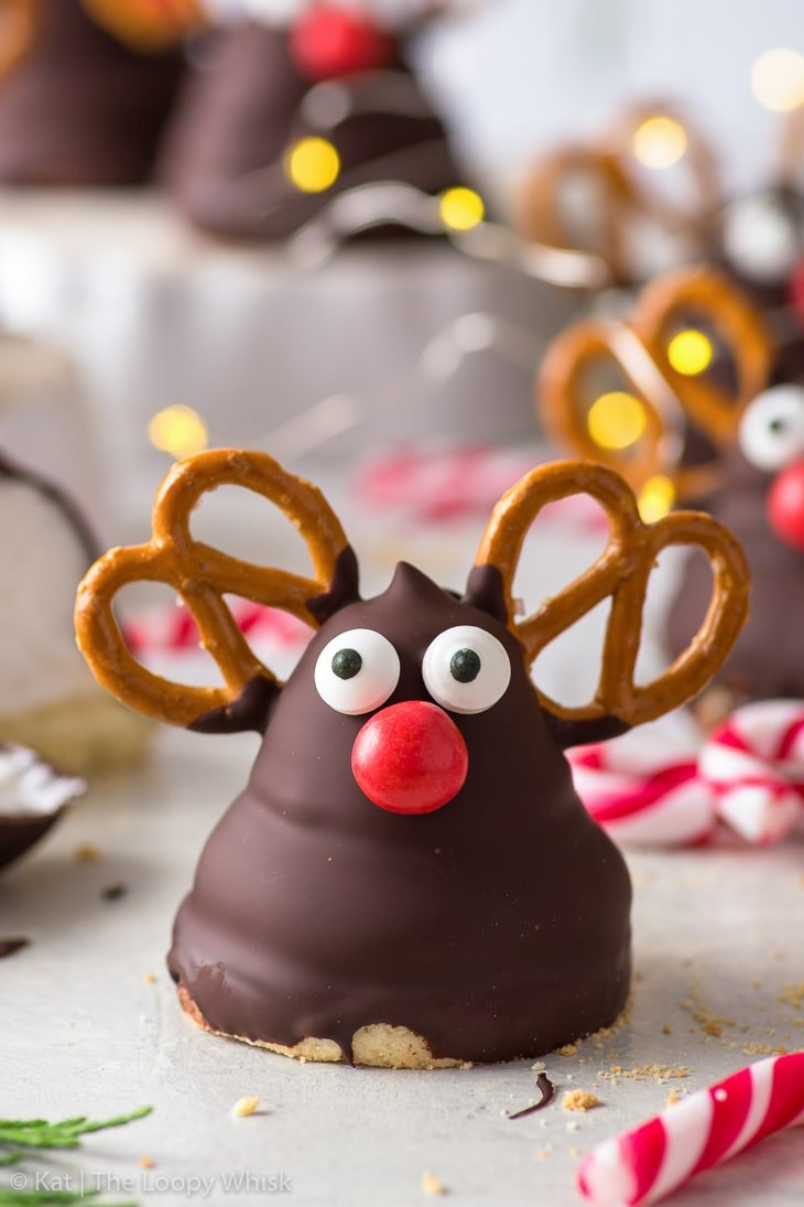 Close-up of a Rudolph marshmallow cookie, with more cookies and fairy lights in the background.