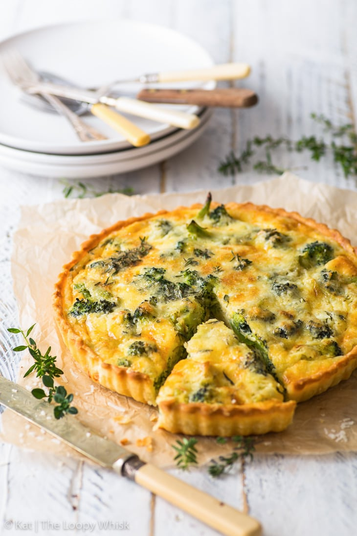 Broccoli quiche on a piece of baking paper, with one piece already cut.
