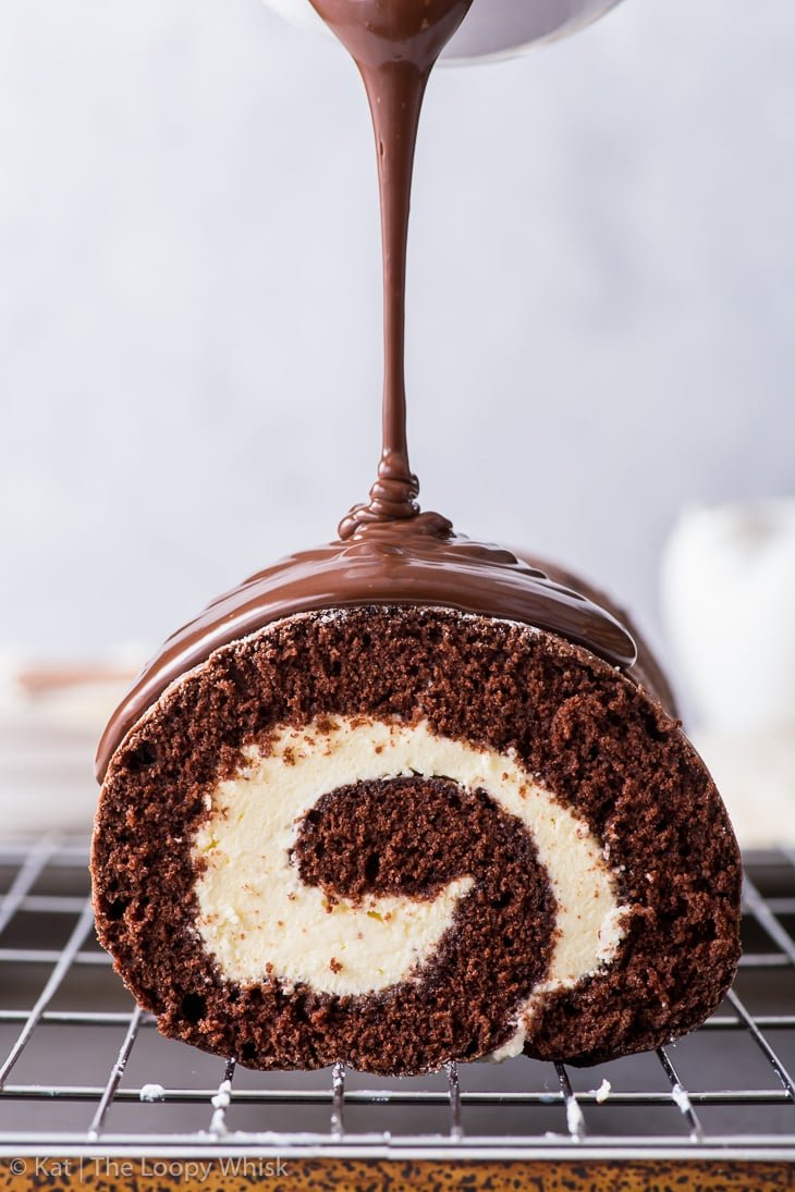 The process of drizzling the chocolate Swiss roll with the chocolate ganache glaze.