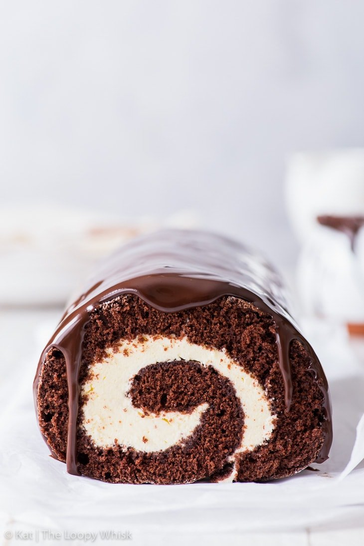 Head-on view of the chocolate Swiss roll, the swirl pattern clearly visible and the chocolate ganache glaze dripping down the sides.