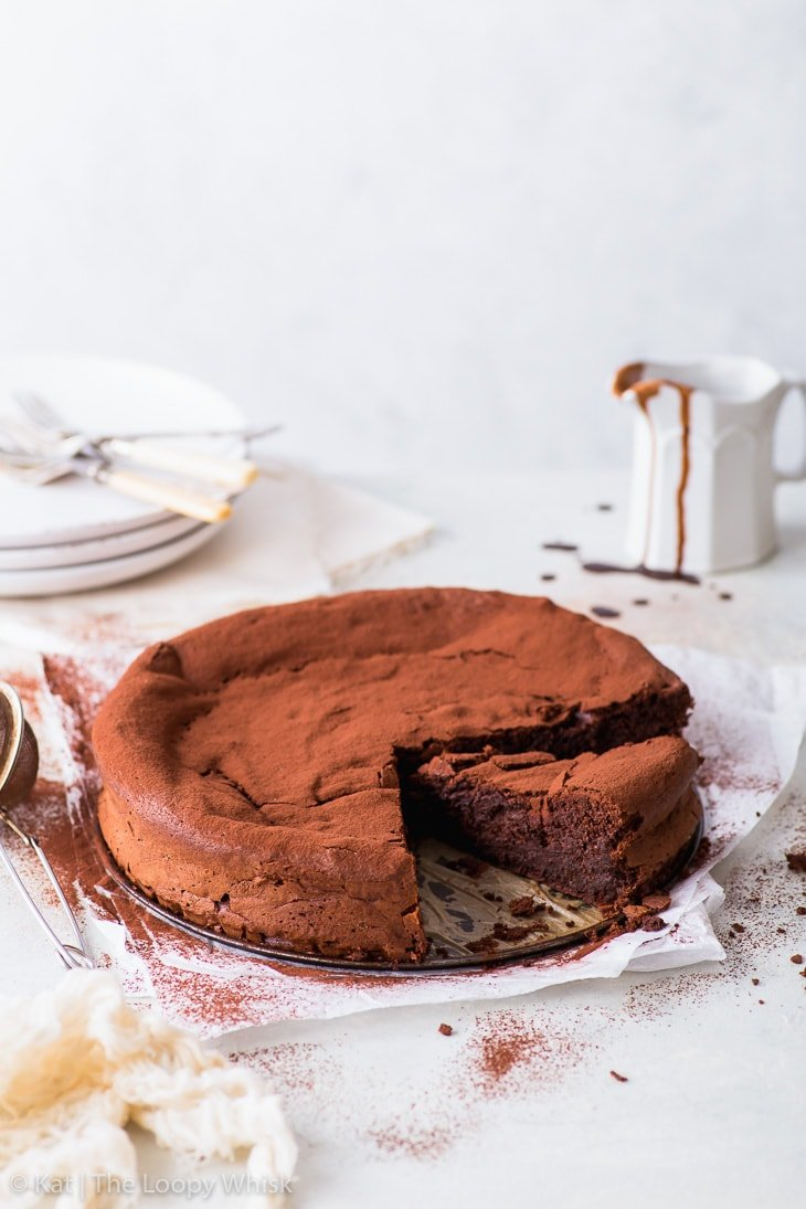 Flourless chocolate cake dusted with cocoa powder and a few pieces already cut, on a white surface with plates and a saucer with chocolate sauce in the background.