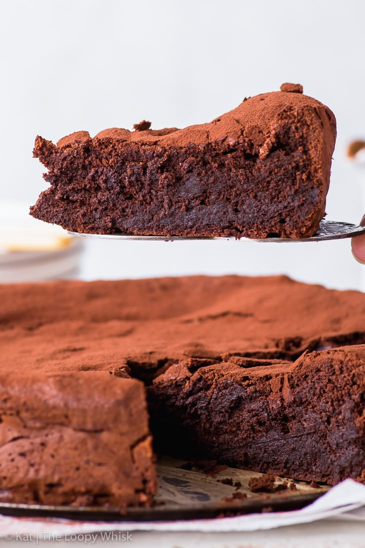Close-up of a piece of the fudgy flourless chocolate cake on a cake server, held above the rest of the cake.