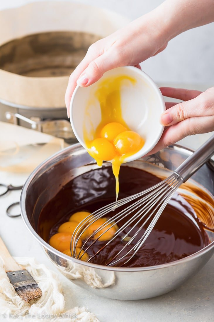 Making a flourless chocolate cake: adding egg yolks to the melted chocolate.