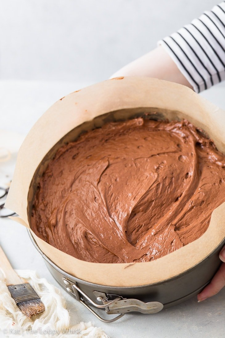Making a flourless chocolate cake: the cake batter with smoothed top in a lined springform pan just before going into the oven.