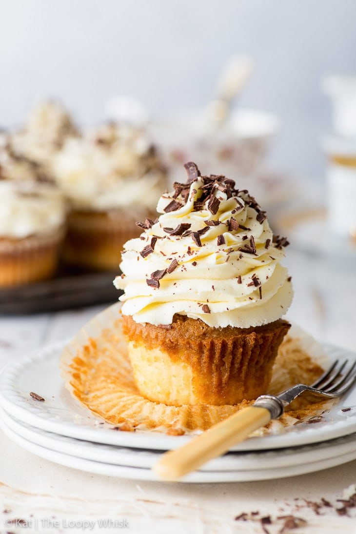 Tiramisu cupcake on a stack of white dessert plates. A fork next to it.