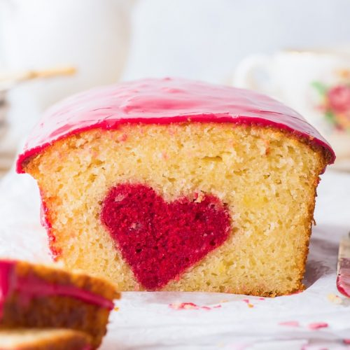 """Hidden Heart Valentine's Cake (Gluten Free) - Simple to make and guaranteed to impress – this """"hidden heart"""" Valentine's cake should be at the top of your Valentine's Day desserts list. A gorgeous, delicate lemon sponge meets a raspberry flavoured hidden design, and the pretty pink raspberry drizzle finishes off a truly wonderful (gluten free!) dessert. Valentine's desserts. Valentine's recipes. Heart cake. Loaf cake recipe. Gluten free cake recipe. Lemon cake. #valentinescake #glutenfree"""