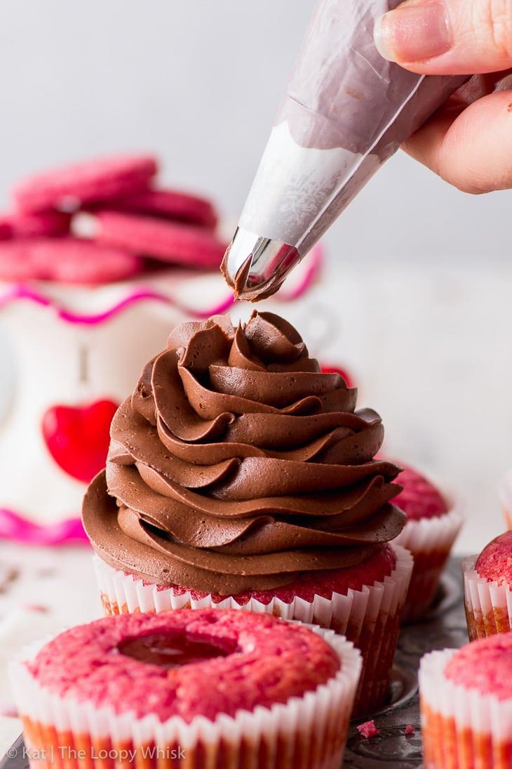 Piping the chocolate buttercream onto raspberry cupcakes, a close-up.