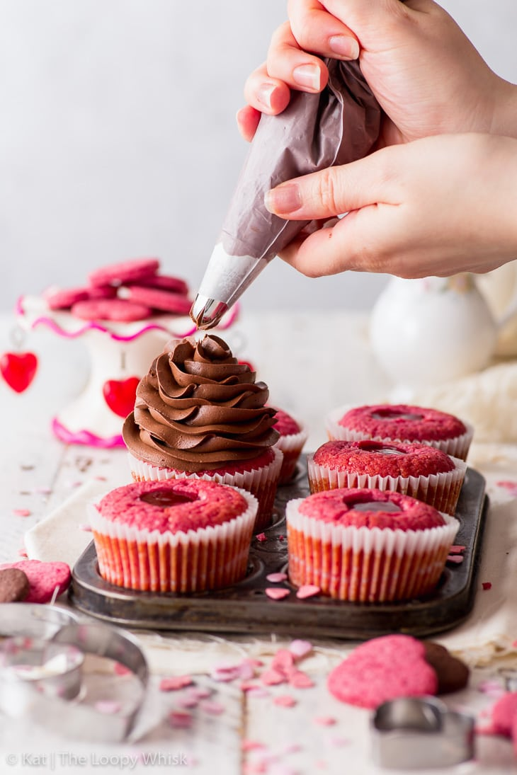 Piping the chocolate buttercream onto raspberry cupcakes.