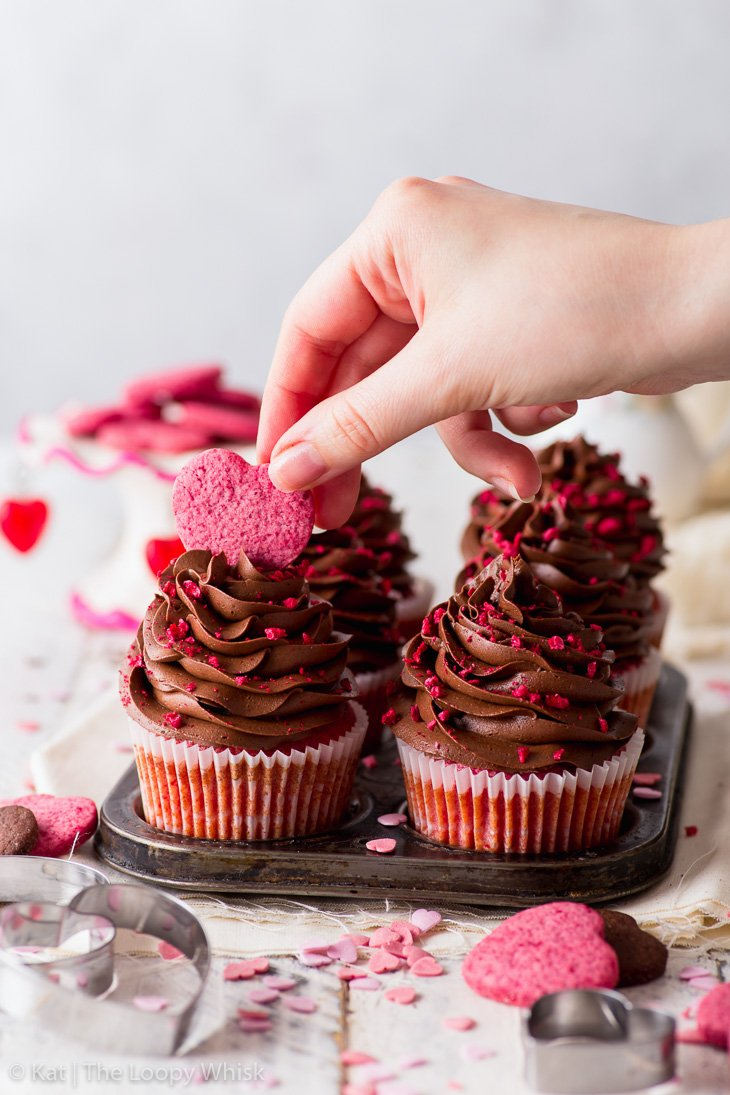 Decorating the Valentine's cupcakes with heart-shaped cookies.