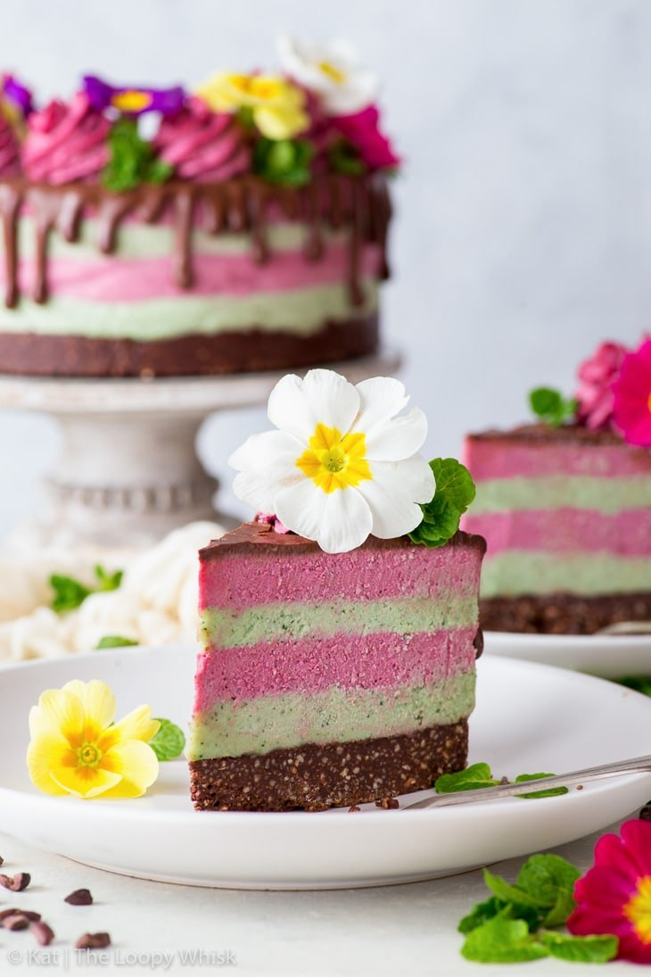 A piece of the raw vegan cake decorated with edible flowers on a white plate. Another piece and the rest of the cake are in the background.