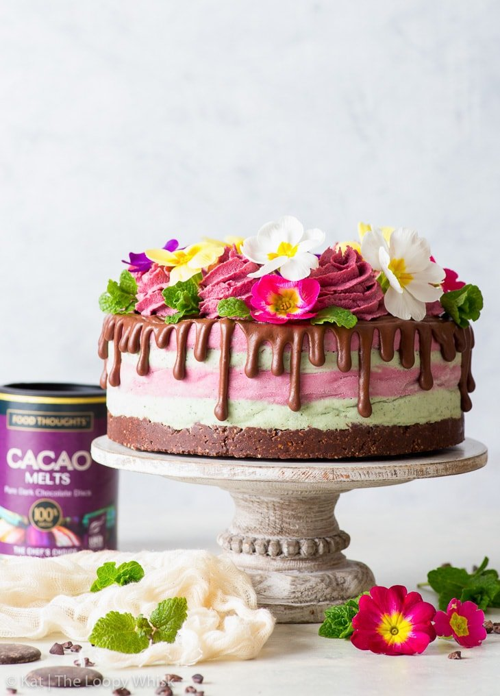 Colourful raw vegan cake decorated with edible flowers on a white cake stand.