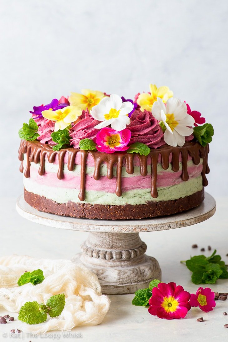 Colourful raw vegan cake decorated with edible flowers on a white cake stand, surrounded by mint leaves and more flowers.