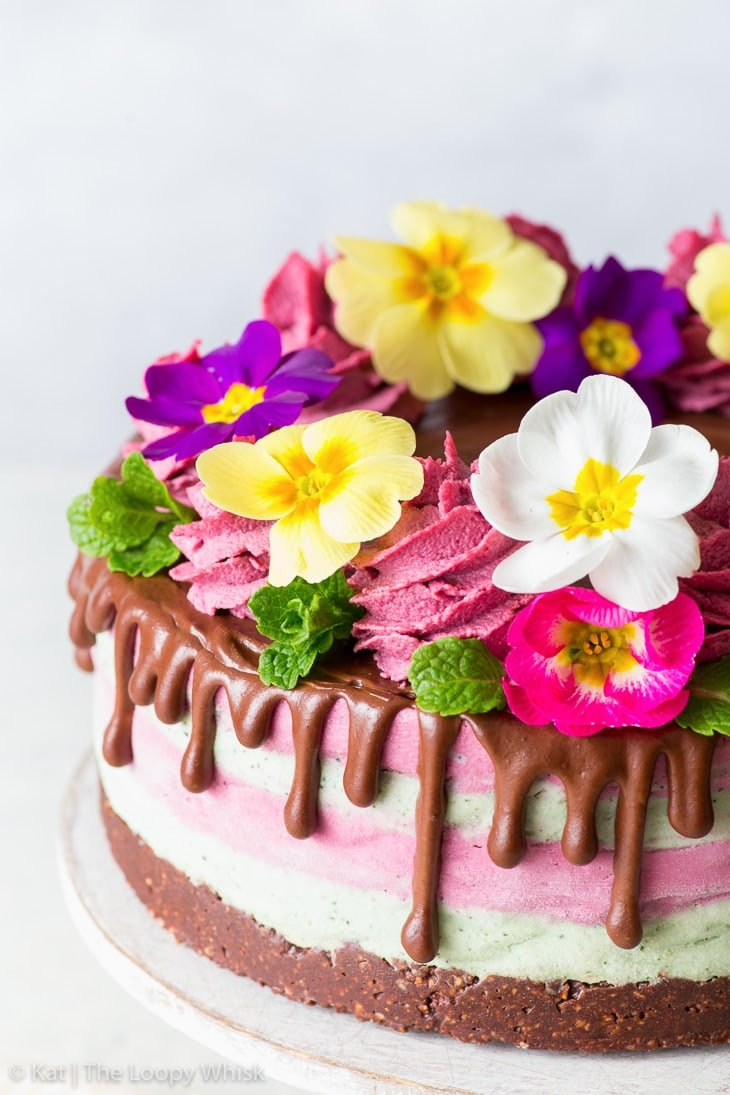 Close-up of the top of the raw vegan cake, decorated with a cacao drip, swirls of piped cashew cream, mint leaves and edible flowers.