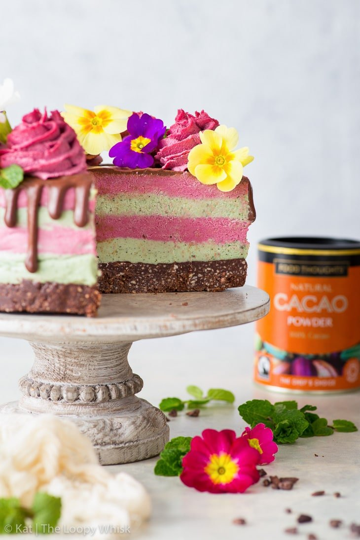 Side-on view of the cut raw vegan cake, showing off the alternate pastel pink and green layers.