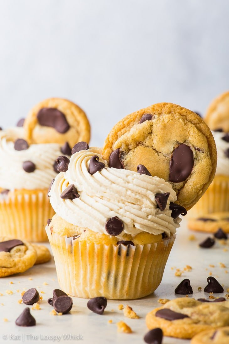 Chocolate chip cupcakes, decorated with buttercream and cookies, on a white surface and in front of a white background.
