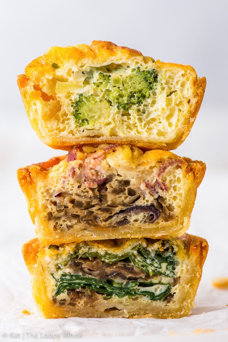 Close-up of a small tower of three different mini quiche halves.