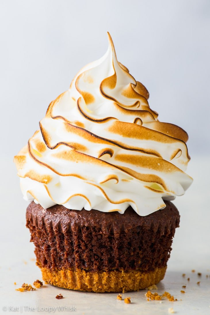 S'mores cupcake with a graham crust bottom, brownie cupcake middle and a toasted Swiss meringue top on a white surface.