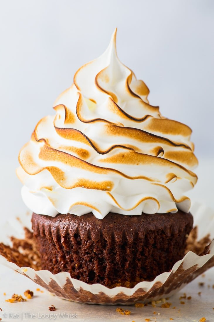 S'mores cupcake with a graham crust bottom, brownie cupcake middle and a toasted Swiss meringue top, with a partially peeled cupcake liner.