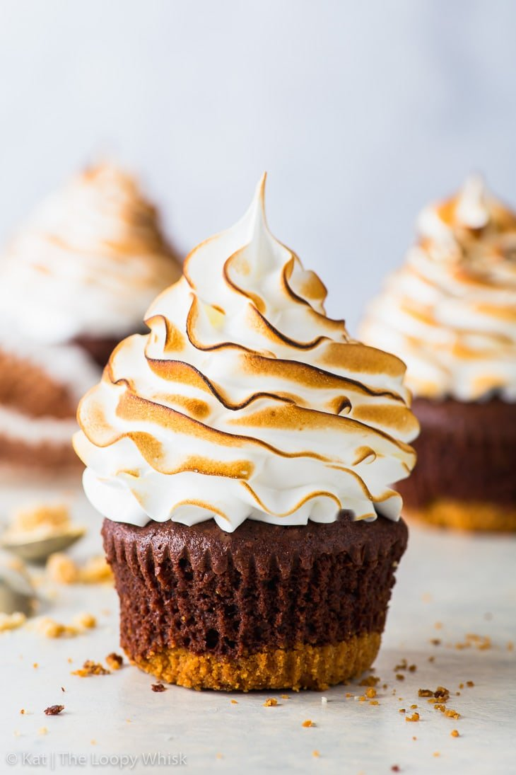 S'mores cupcake with a graham crust bottom, brownie cupcake middle and a toasted Swiss meringue top. More cupcakes are in the background.