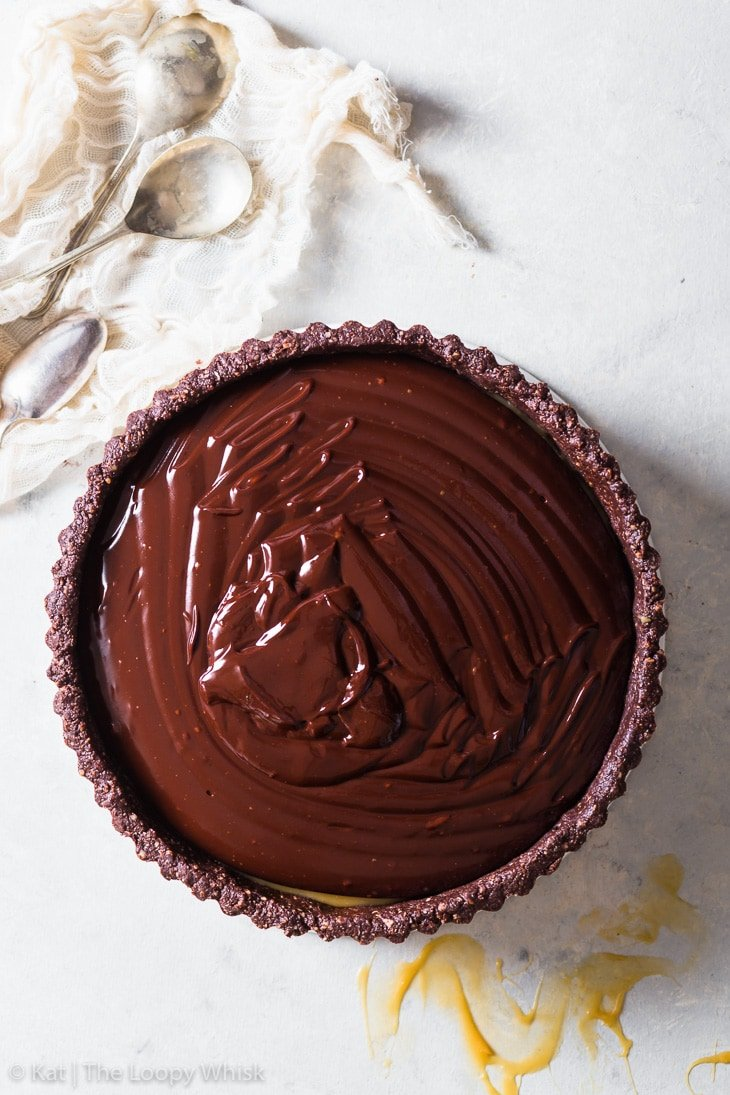 Overhead view of the chocolate ganache, just after it's been poured on top of the salted caramel layer of the tart.