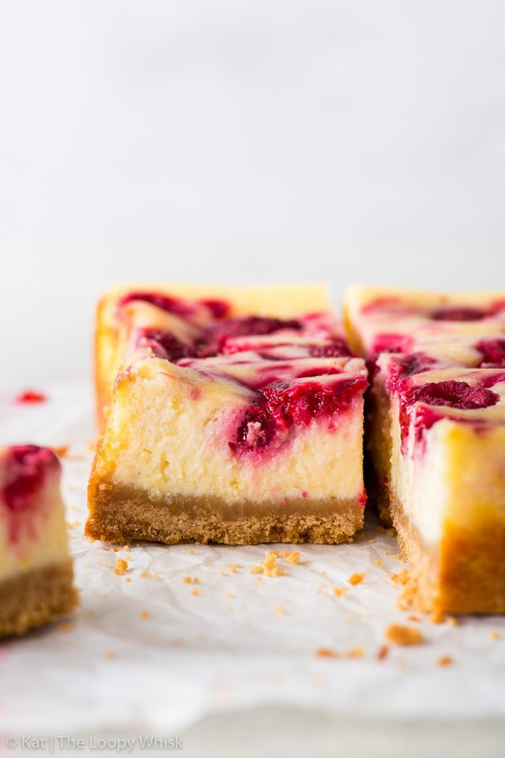 Raspberry cheesecake bars on a piece of white parchment paper.