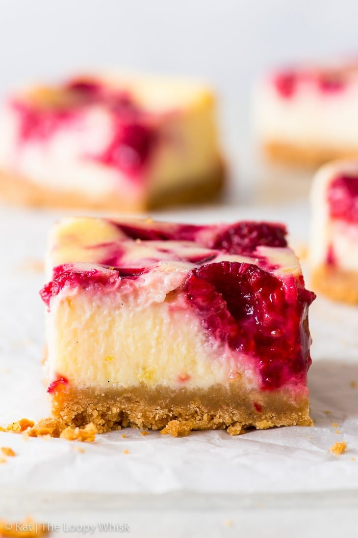 A raspberry cheesecake bar on white parchment paper. More bars are in the background.