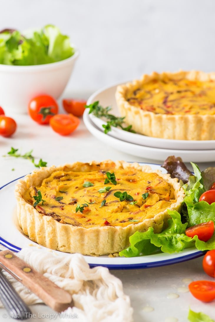 Vegan quiche on a plate with green salad leaves and cherry tomatoes. Another quiche is in the background.