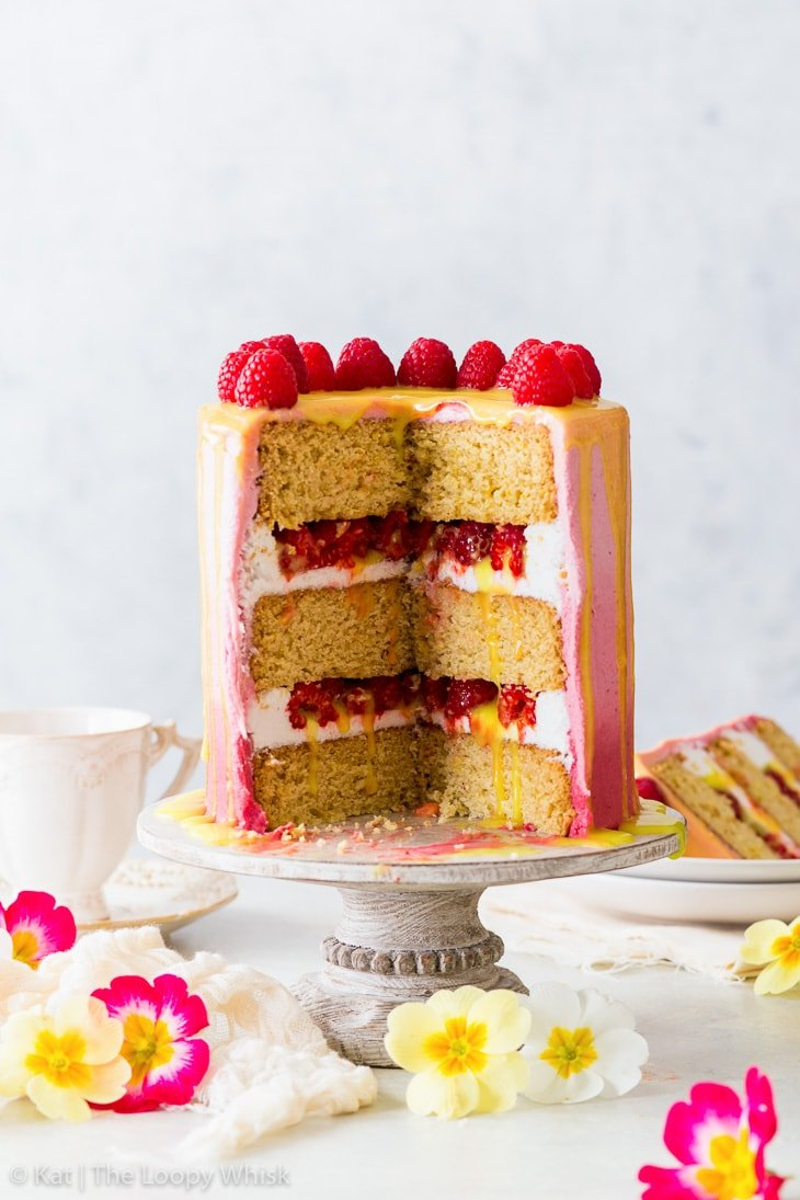 Vegan raspberry & lemon cake on a white cake stand, with a few slices having been already cut. The layered interior of the cake can be seen.