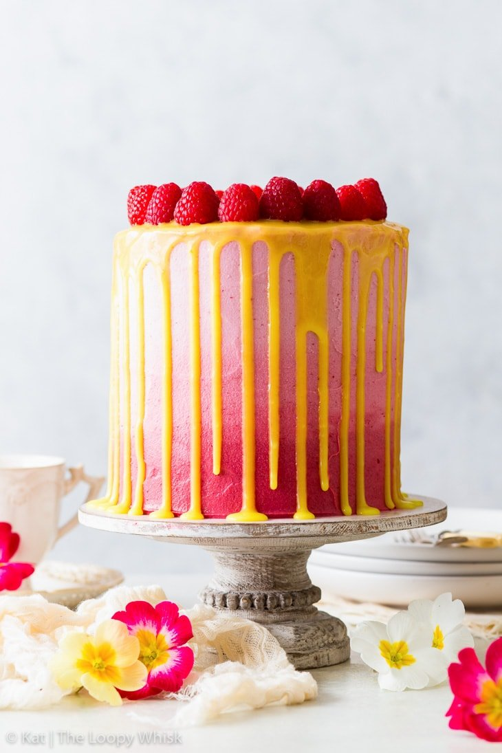 Vegan raspberry & lemon cake, decorated with pink ombre frosting and a bright yellow lemon curd drip, on a white cake stand. Colourful spring flowers are arranged around the cake stand.