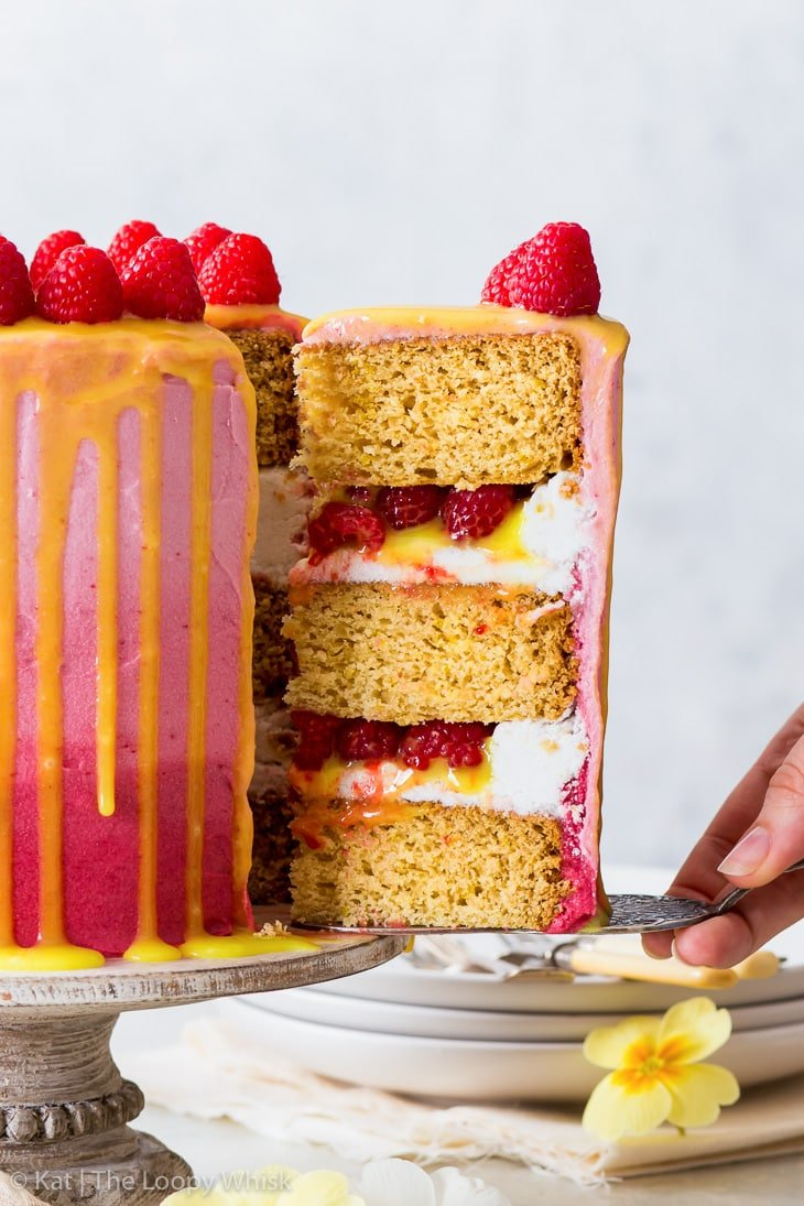 Cutting a piece of the vegan raspberry & lemon cake, showing all the layers.