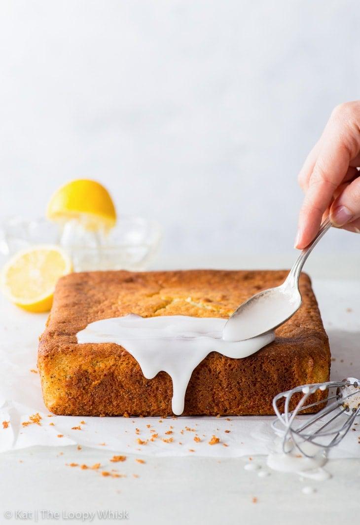 Spreading lemon icing on top of the lemon poppy seed cake.