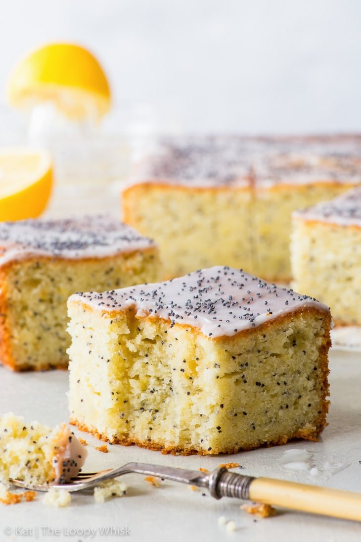 Pieces of lemon poppy seed cake on a piece of parchment paper, with a lemon and a glass juicer in the background. The piece in the foreground is being eaten.