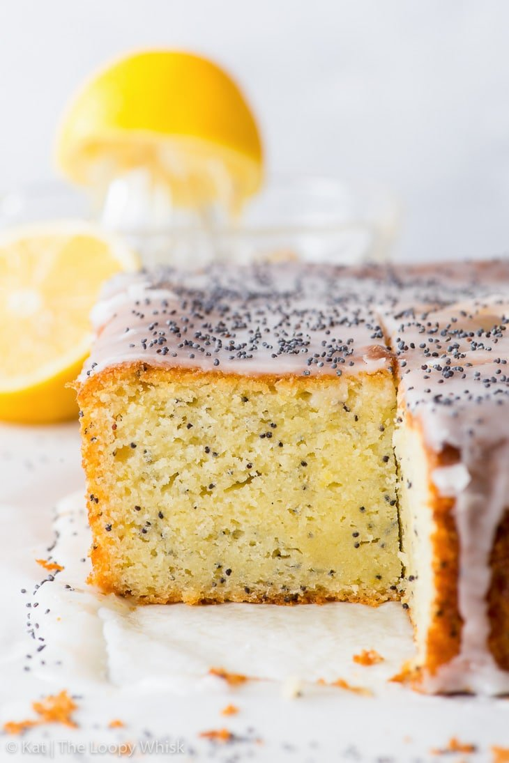 A piece of the lemon poppy seed cake has been cut, showing the fluffy yellow cake crumb inside.