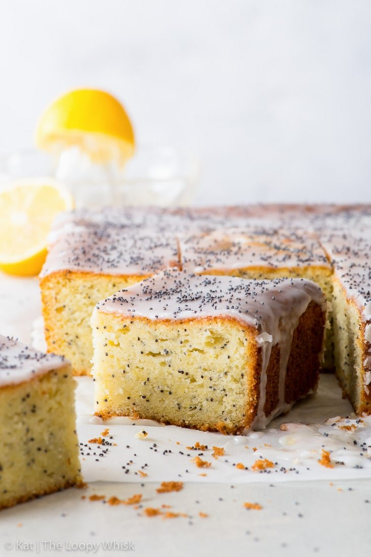 Pieces of lemon poppy seed cake on a piece of parchment paper, with a lemon and a glass juicer in the background.