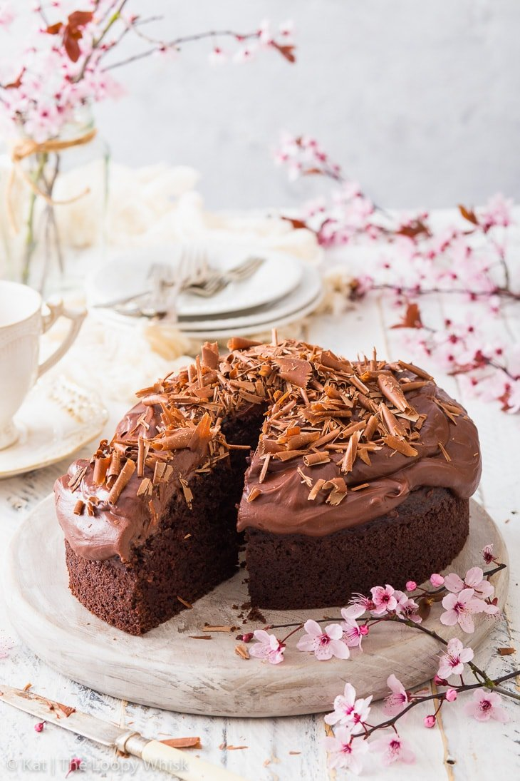 Vegan chocolate cake on a white wooden board, surrounded by cherry blossom branches. A piece has been cut from the cake.