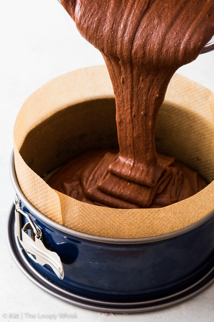 Pouring the vegan chocolate cake batter into a lined cake tin.