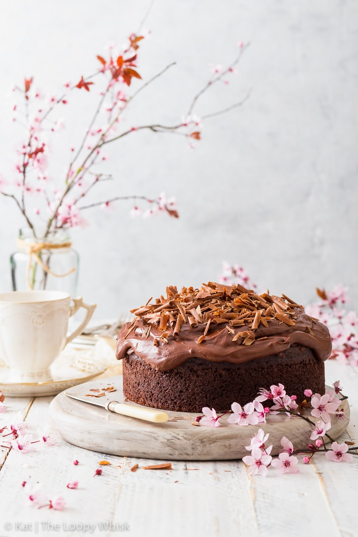 Vegan chocolate cake on a white wooden board, surrounded by cherry blossom branches.
