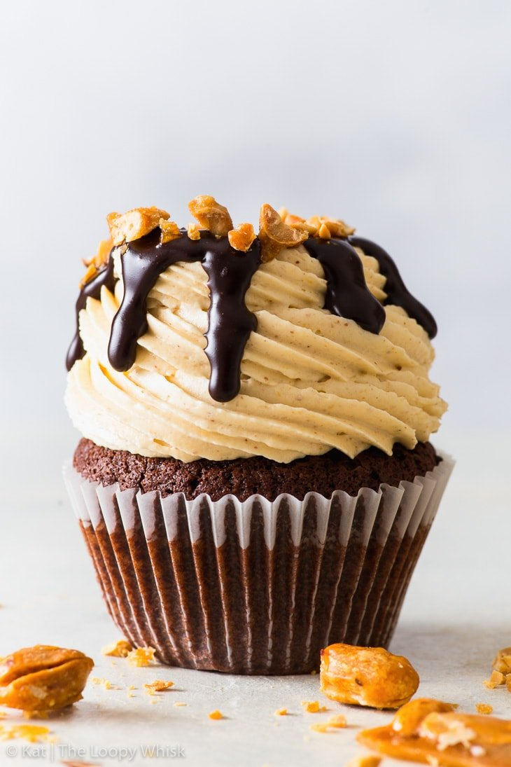 Peanut butter chocolate cupcake drizzled with chocolate fudge sauce and decorated with chopped candied peanuts on a light backdrop.