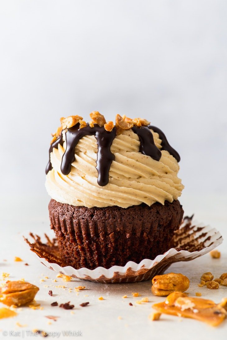 Peanut butter chocolate cupcake drizzled with chocolate fudge sauce and decorated with chopped candied peanuts on a light backdrop, with the cupcake case partially unwrapped.