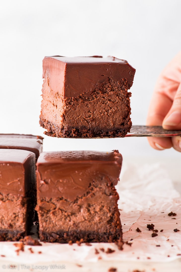 Triple chocolate cheesecake bar being lifted with a cake server.